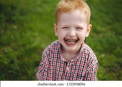 A young dirty boy with chocolate on his face on a green background who is laughing.