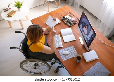 Young disable female teacher consulting online student and explaining notes in copybook while sitting in wheelchair by computer