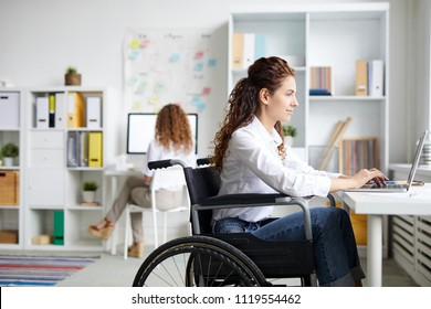 Young disable office worker in wheelchair sitting by desk in front of laptop and networking