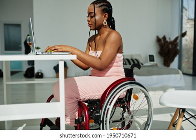 Young disabled African American woman in wheelchair at home working with laptop.