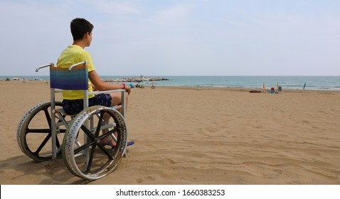 young disabled boy on the beach and the special wheelchair