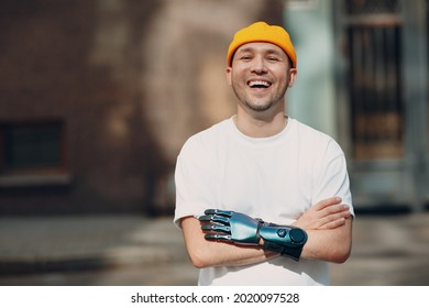 Young disabled man with artificial prosthetic hand in casual clothes laughing portrait