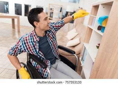 A young disabled man is cleaning himself at home. He is sitting in a wheelchair. He wipes a bookshelf from the dust, using a brush from dust and a sponge.
