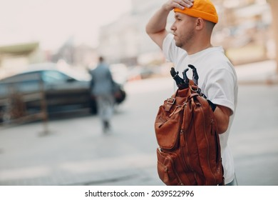 Young disabled man hold backback leather bag with artificial prosthetic hand in casual clothes