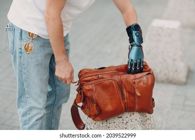 Young disabled man hold and zips backback leather bag with artificial prosthetic hand in casual clothes