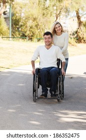 Young disabled man on a wheelchair walking with his girlfriend in the park