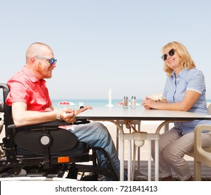 Young disabled man sits with a woman at a table on the beach