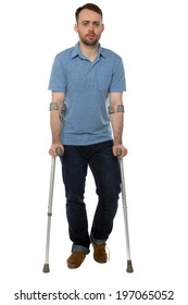 Young disabled man wearing casual clothes while walking with forearm crutches during recovery, full length, on white