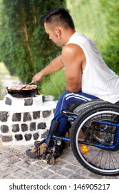 Young disabled man in wheelchair enjoying a Barbecue at summer