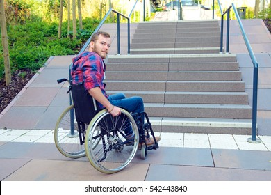 young disabled man in wheelchair in front of stairs