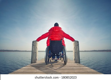 Young disabled man in wheelchair on a boardwalk on lake enjoying his freedom