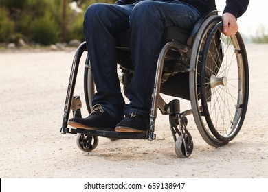 Young disabled man in wheelchair smile outside.