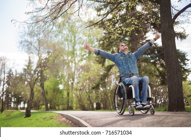 young disabled man in wheelchair walking park