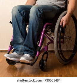 Young disabled paraplegic man in grey shirt, blue jeans and white trainers shoes sitting in wheelchair ir house room, disability concept