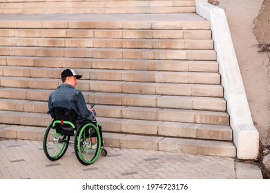 a young disabled person in a wheelchair can not enter the stairs. Accessible environment for the disabled