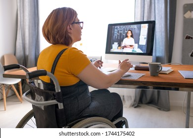 Young disabled tutor sitting in wheelchair and helping black student girl with hometask online while working remotely