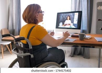 Jeune tutrice handicapée assise en fauteuil roulant et aidant une étudiante noire à faire un travail à domicile en ligne tout en travaillant à distance