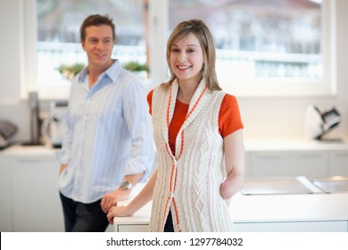Young disabled woman with amputee arm in kitchen with man smiling at camera