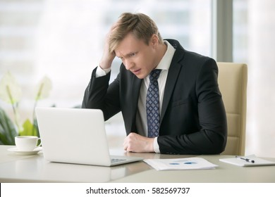 Young disappointed businessman working at office desk, feeling stressed, looking at laptop pc screen in panic, received bad news, unable to keep company afloat, having not enough cash to run business