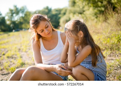 Young disappointed girl kid being consoled by her elder sister
