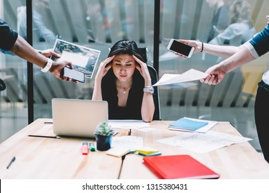 Young disappointed woman feeling headache from deadline surrounded by colleagues at workplace, multi-purpose female employee,tired of work and exhausted, stress in office. Overworked female in confuse