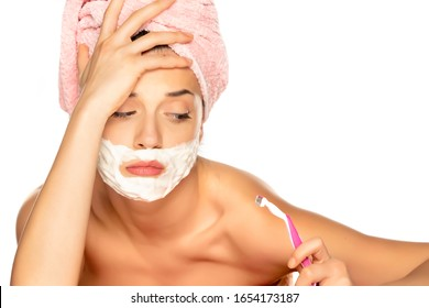 Young disappointed woman shaves her face on white background