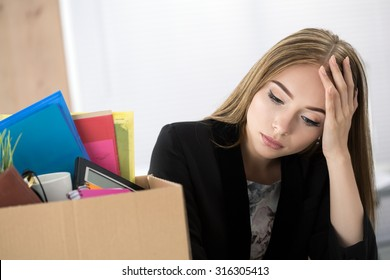 Young dismissed female worker in office sitting near carton box with her belongings. Getting fired concept.