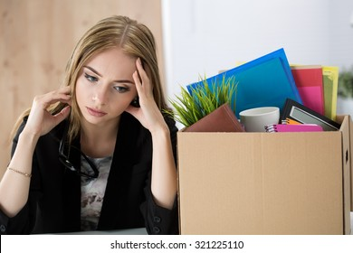 Young dismissed female worker sitting near the carton box with her belongings in office not knowing what to do next. Getting fired concept.