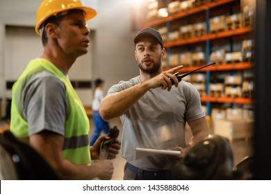 Young dispatcher communicating about delivery schedule with warehouse worker in factory warehouse.