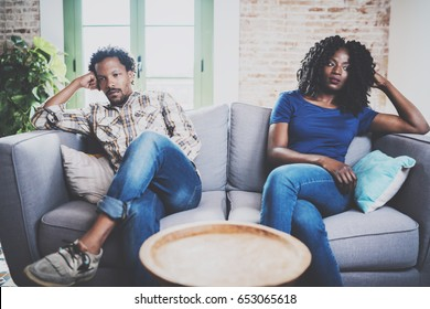 Young displeased black couple.American african men arguing with his stylish girlfriend,who is sitting on sofa on couch next to him with legs crossed.Man looking away offended expression on her face