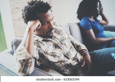 Young displeased black couple.Upset man being ignored by partner at home in the living room.American african men arguing with his stylish girlfriend,who is sitting on sofa couch next to him.Blurred.