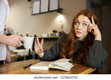 A young displeased girl is sitting in the cafe. She is refusing a cup of coffee while scornfully looking away.