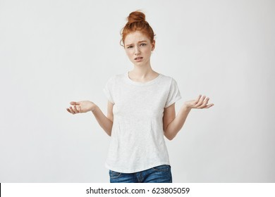 Young displeased redhead girl gesturing looking at camera. Confused girl arguing with a boyfriend. White background.