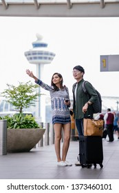 A young and diverse Asian couple (Korean man and his Indian girlfriend) hail to flag their ride that they booked via a ride hailing app to go to the city. They are standing at the pickup point.