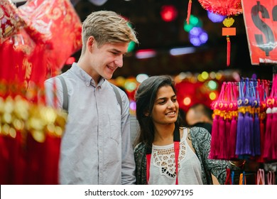 A young diverse interracial couple (Indian woman, Caucasian man) browse trinkets at the night market during the Chinese New Year festival in Asia. They are tourists and are smiling and having fun.