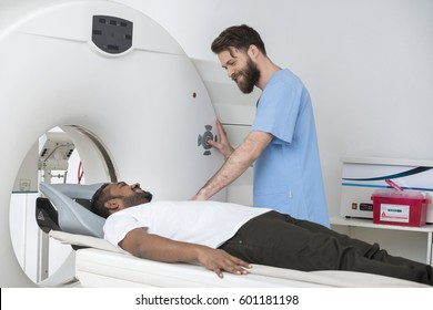 Young Doctor About To Start CT Scan On Man In Hospital