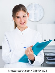 Young doctor assistant standing in medical office noting prescriptions