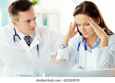 Young doctor being nervous about her mistake, senior doctor trying to console her