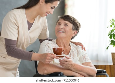 Young doctor bringing a cup of herbal tea to a happy patient resting after difficult treatment