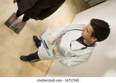 A young doctor, checks his patients weight on a scale. - horizontally framed