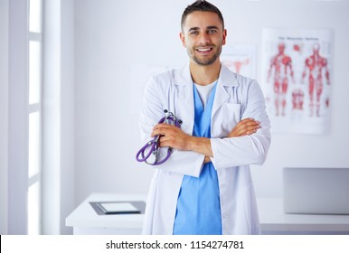 Young doctor with coffee cup in medical office