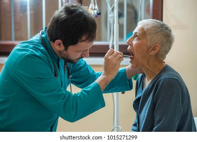 Young doctor examining his patient's throat with a wood stick