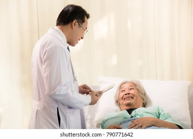 Young doctor has a treatment for senior woman patient in sickbed,