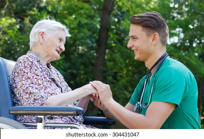 Young doctor helping a handicapped elderly woman
