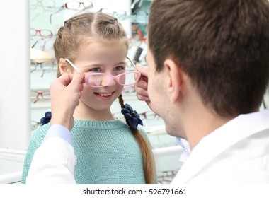 Young doctor helping little girl to choose new glasses in shop