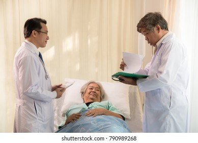 Young doctor and his assistant have a treatment for senior woman patient in sickbed,