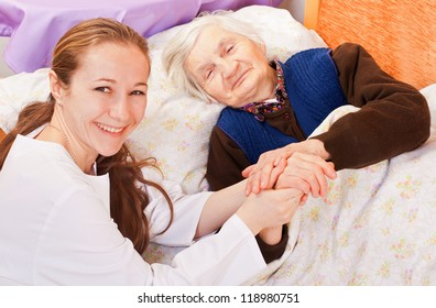 Young doctor holds the old woman's hands