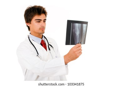 Young doctor looking to x-ray , isolated on white