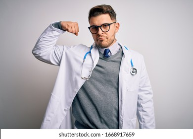 Young doctor man with blue eyes wearing medical coat and stethoscope over isolated background Strong person showing arm muscle, confident and proud of power