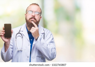 Young doctor man showing smartphone screen over isolated background serious face thinking about question, very confused idea